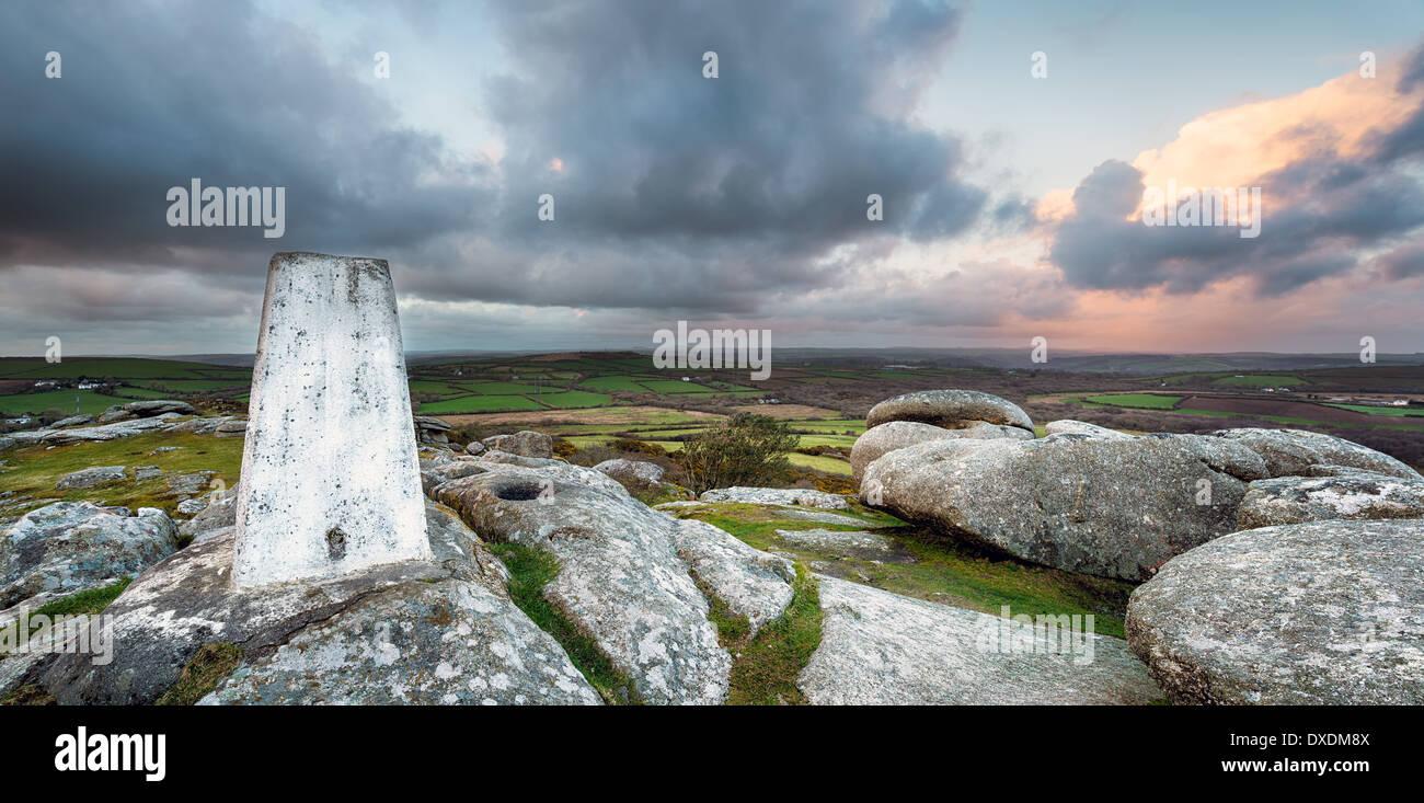 Un punto Trig para asignar la triangulación bajo un cielo tormentoso en la parte superior de Helman Tor en Cornwall. Foto de stock