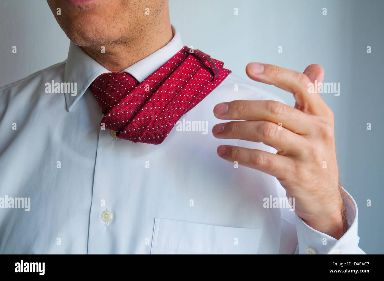 Hombre empujando su corbata a su espalda. Cerrar vista. Imagen De Stock