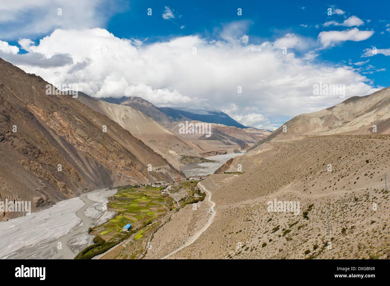 Vista en un profundo valle, arroyo torrencial, valle de Kali Gandaki, exuberantes campos verdes que rodean la aldea de Kagbeni Imagen De Stock