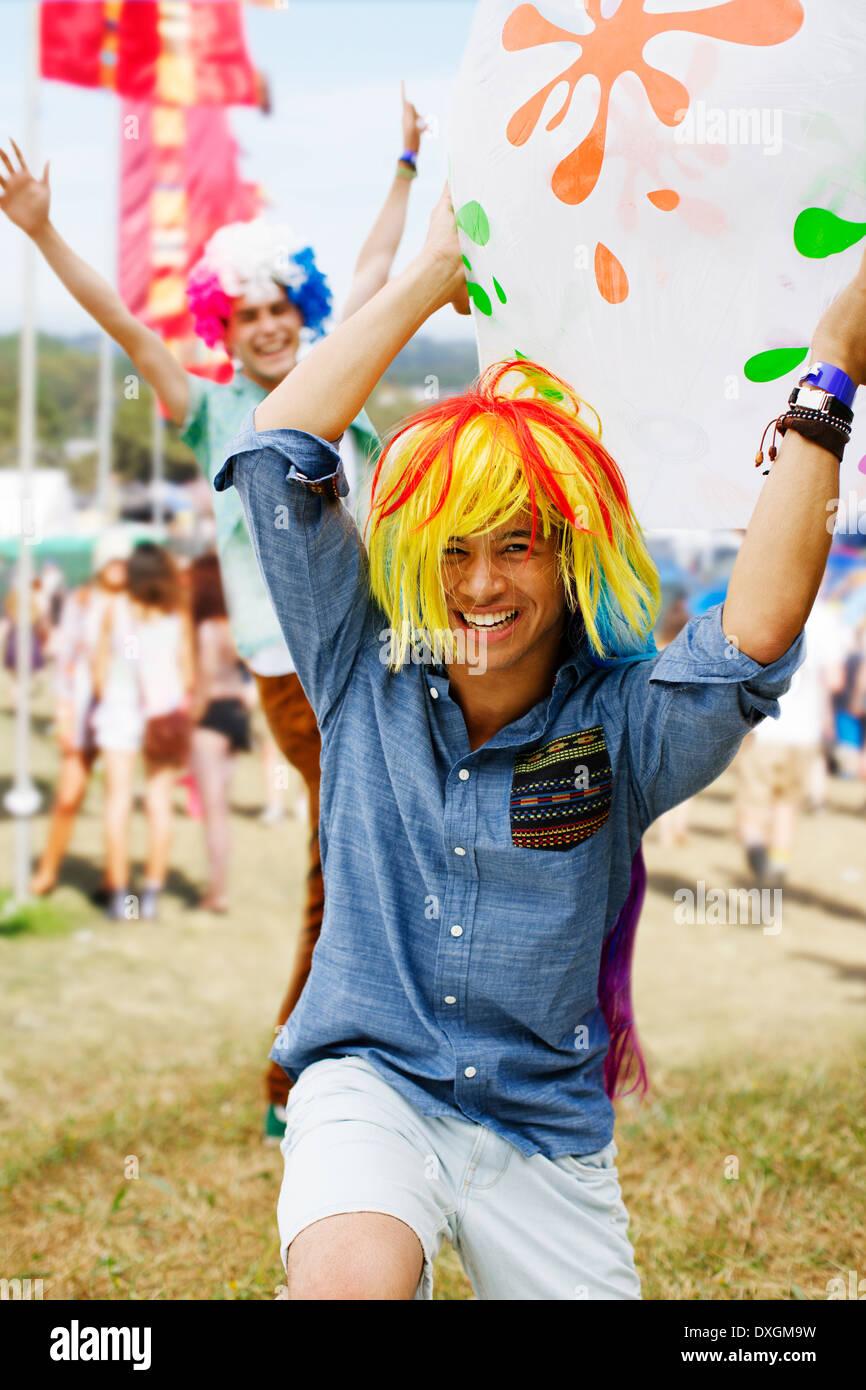 Juguetón hombres vítores en pelucas en festival de música Foto de stock