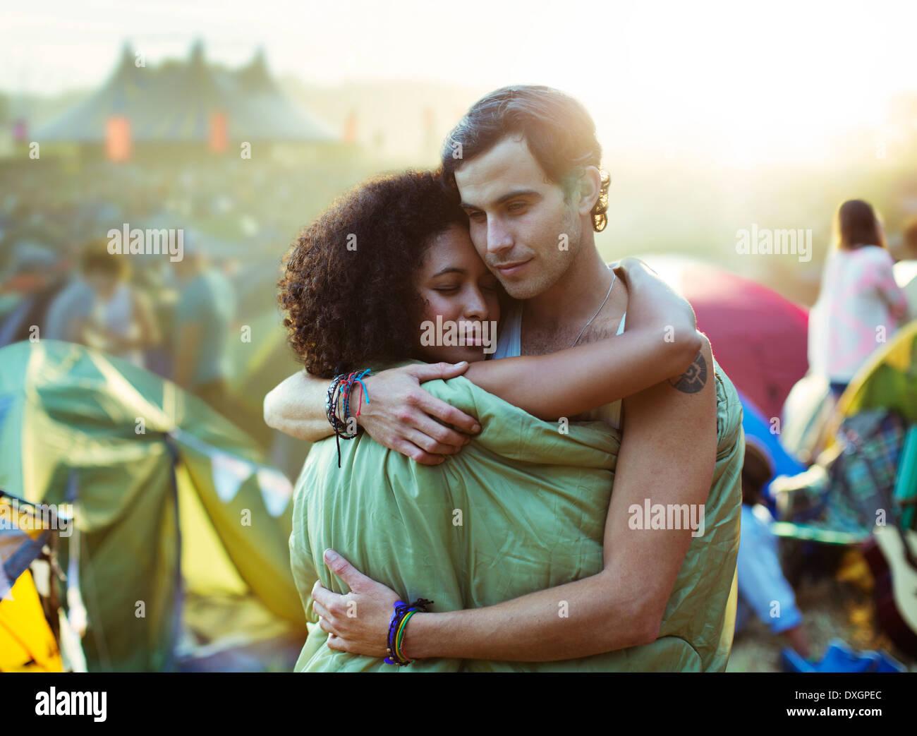 Pareja en saco de dormir abrazando fuera de carpas en el festival de música Imagen De Stock