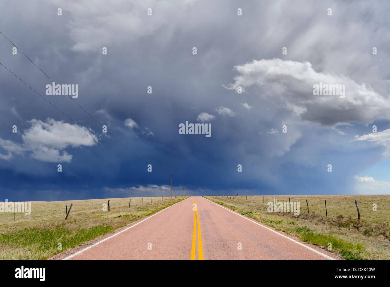 Nubes de tormenta sobre carretera abierta, Rush, Colorado, Estados Unidos Foto de stock