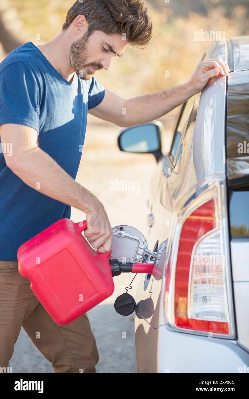Hombre de llenado del depósito de gas al lado de la carretera Imagen De Stock