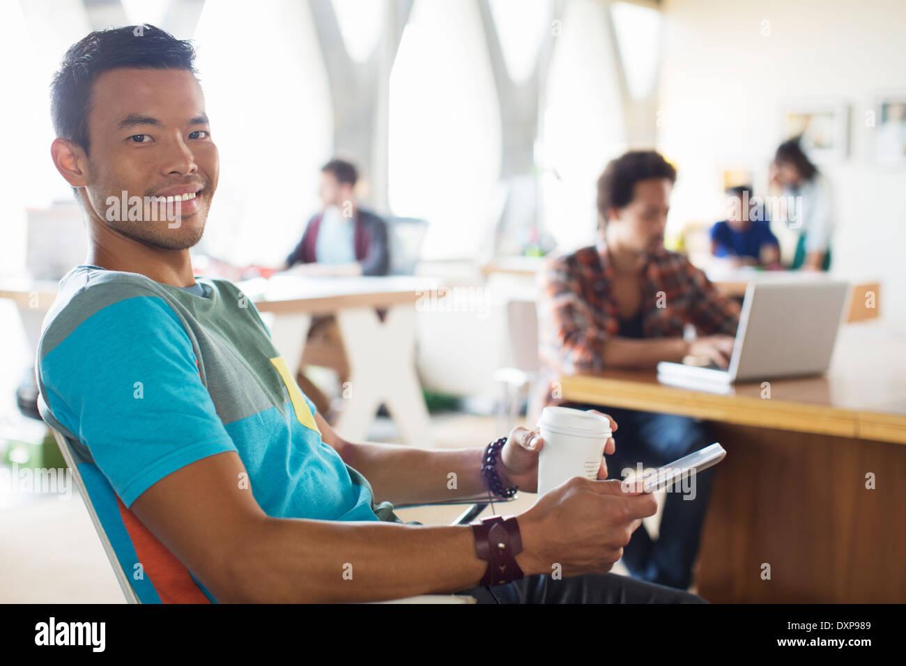 Retrato de sonriente empresario casual bebiendo café y utilizando tablet digital en Office Foto de stock