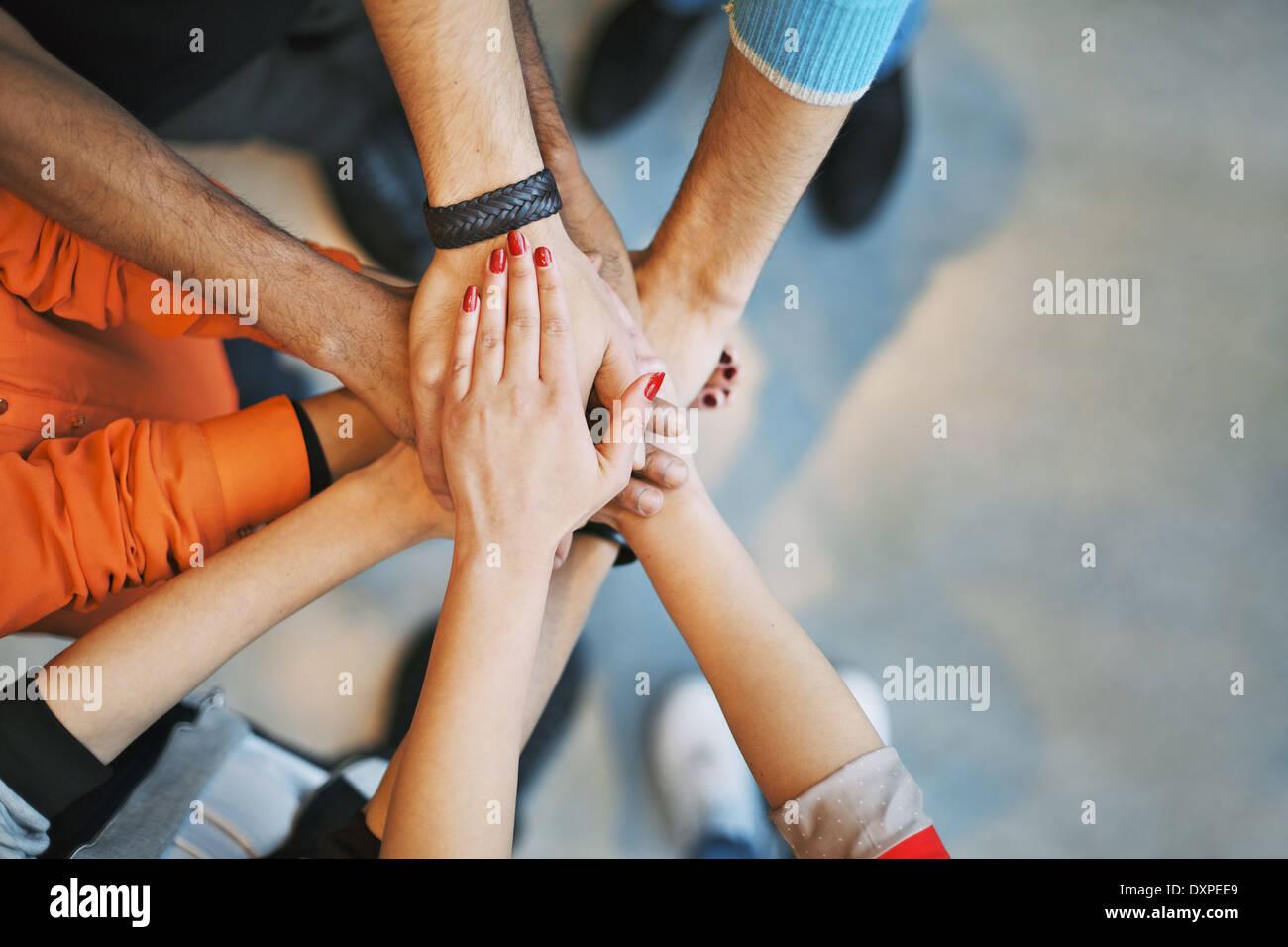 Grupo multiétnico de gente joven poniendo sus manos en la parte superior de cada uno. Cerrar imagen de jóvenes estudiantes manos de apilamiento. Imagen De Stock