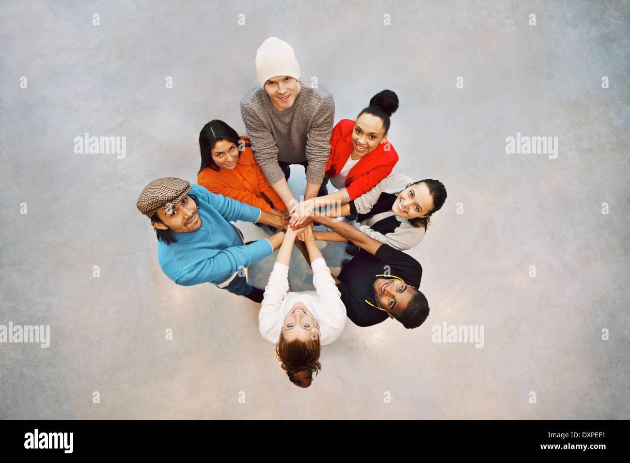 Un grupo de jóvenes estudiantes felices mostrando. Vista superior del grupo multiétnico de gente joven poniendo sus manos juntas. Imagen De Stock