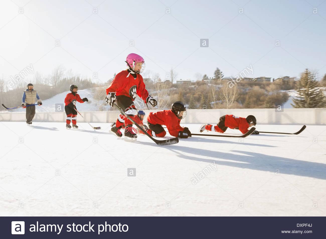 Equipo de hockey sobre hielo de realizar ejercicios de entrenamiento en la pista de patinaje al aire libre Imagen De Stock