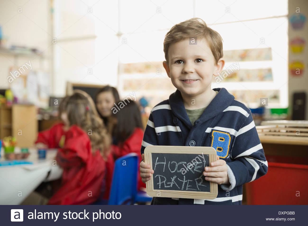 """Elementary niño sosteniendo la pizarra con 'jugador de hockey"""" escrito en él Imagen De Stock"""