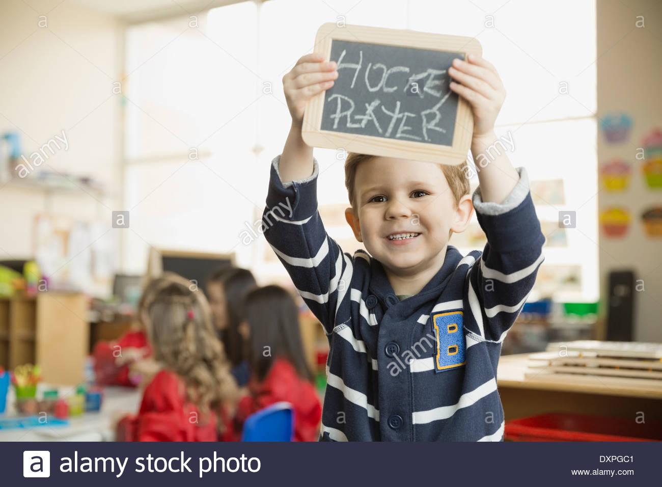 """Sonriente niño sosteniendo la pizarra con 'jugador de hockey"""" escrito en él Imagen De Stock"""