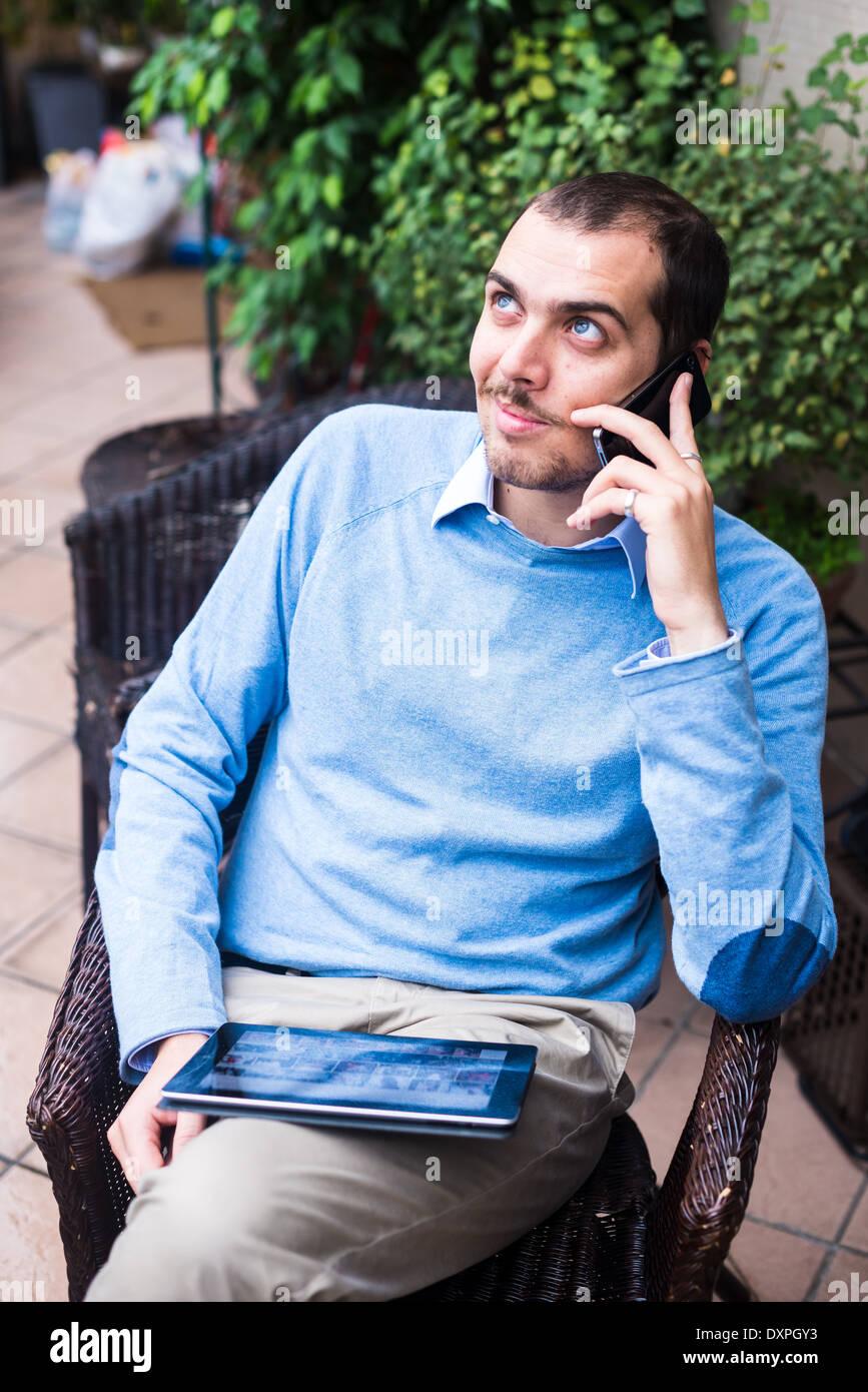 Hombre de negocios elegante multitarea multimedia utilizando dispositivos en casa Foto de stock