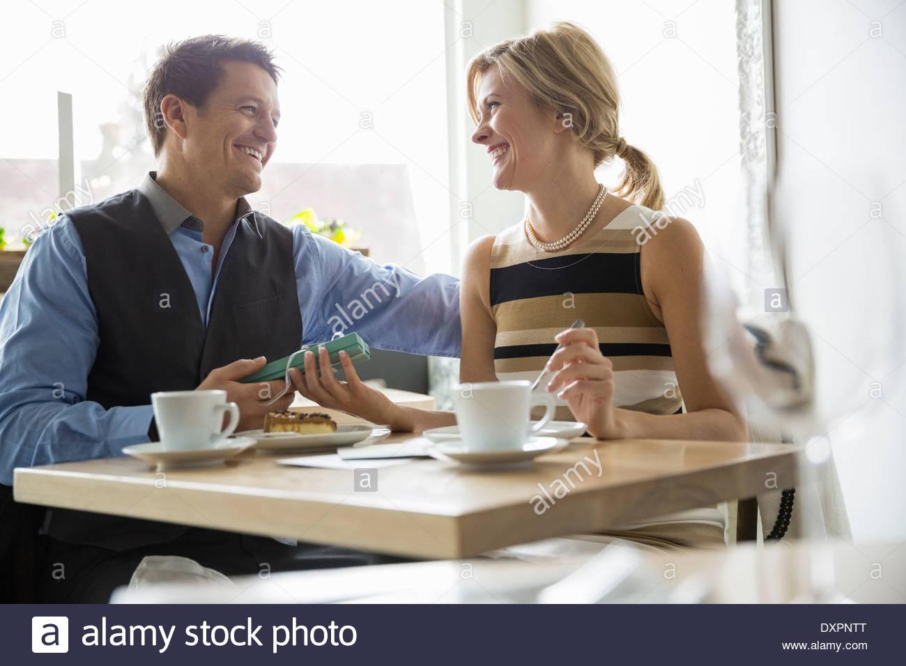 Hombre Mujer sorprendente con el regalo en el bistro tabla Imagen De Stock