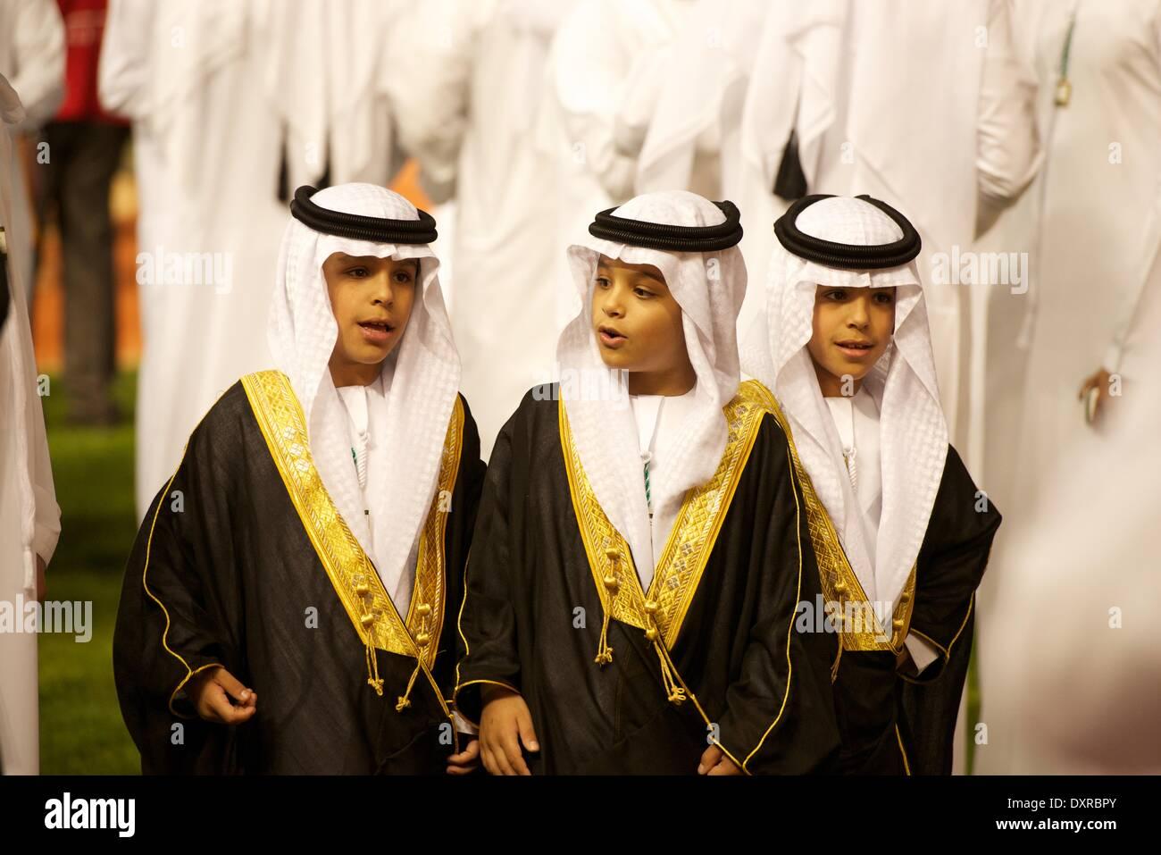 El hipódromo de Meydan, en Dubai, EAU. El 29 de marzo, 2014. Tres jóvenes príncipes saludar a los corredores como entran en el desfile de la corona durante la Copa del Mundo de Dubai Credit: Tom Morgan/Alamy Live News Imagen De Stock