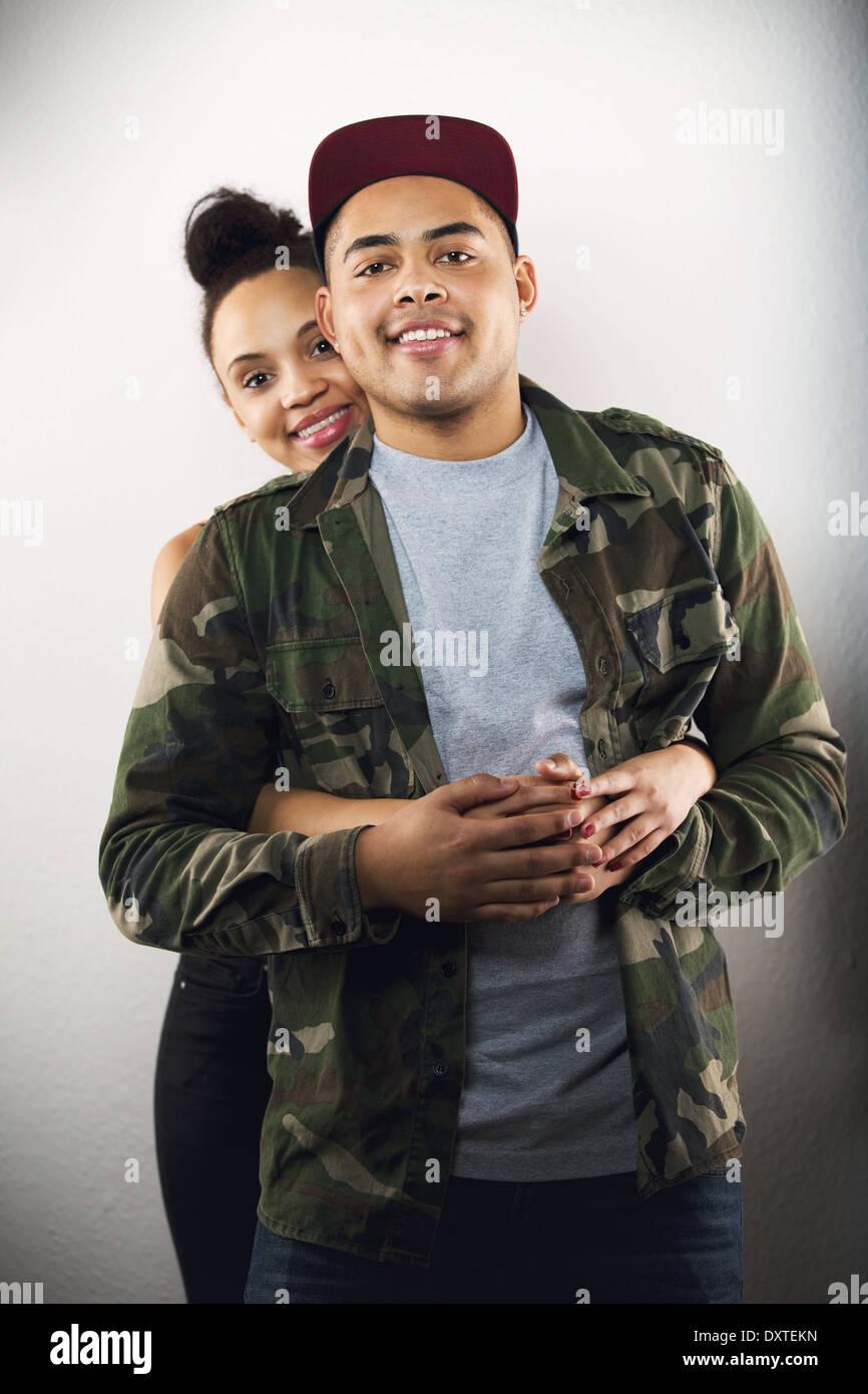 Señorita abrazando a su novio por detrás. Encantadora pareja joven en amor juntos sobre fondo gris. Foto de stock