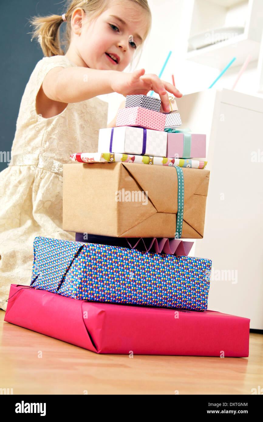 Chica de cumpleaños mirando la pila de regalos, Munich, Baviera, Alemania Imagen De Stock