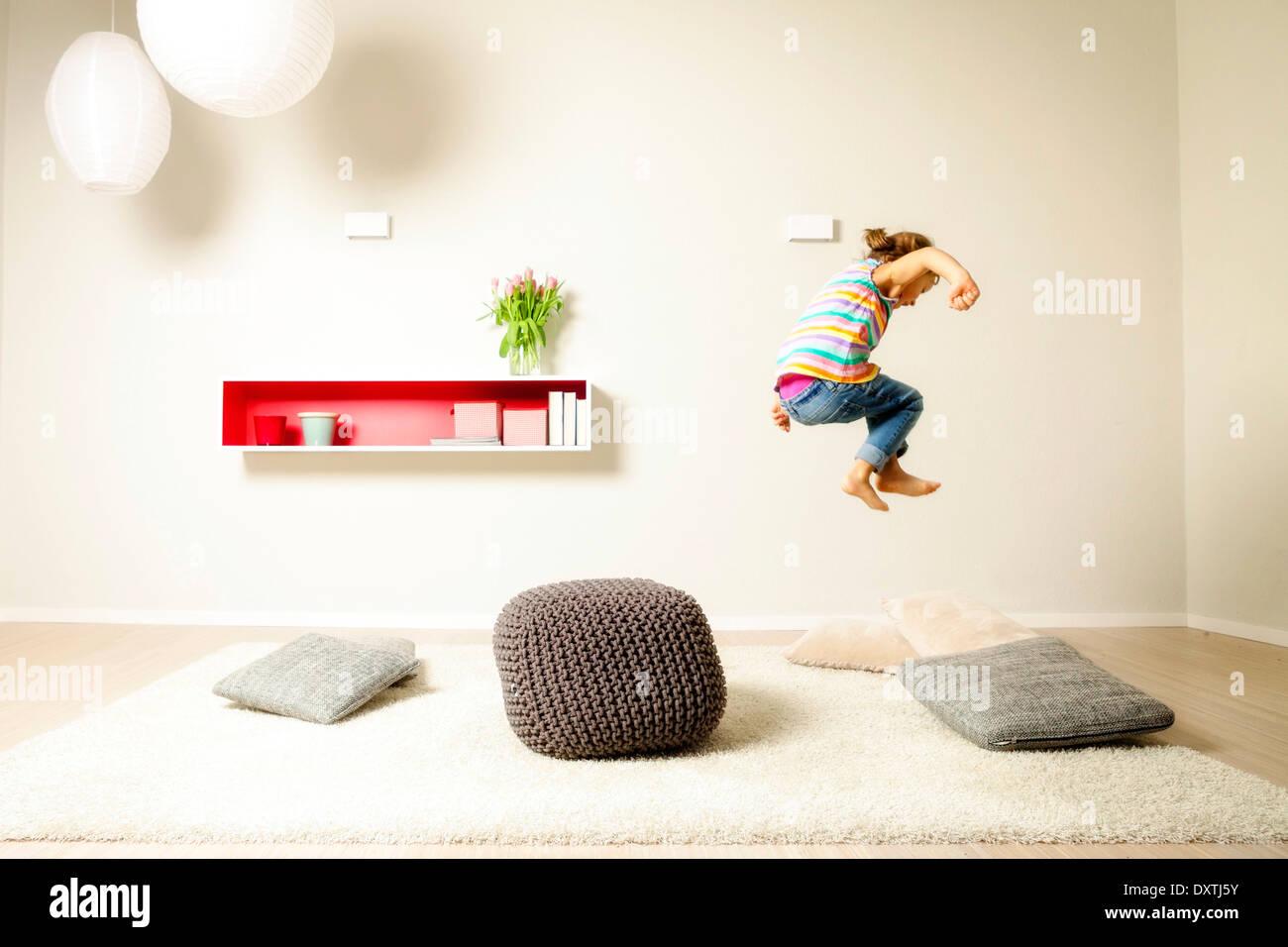 Chica saltando a través de cojines, divertirse, Munich, Baviera, Alemania Imagen De Stock
