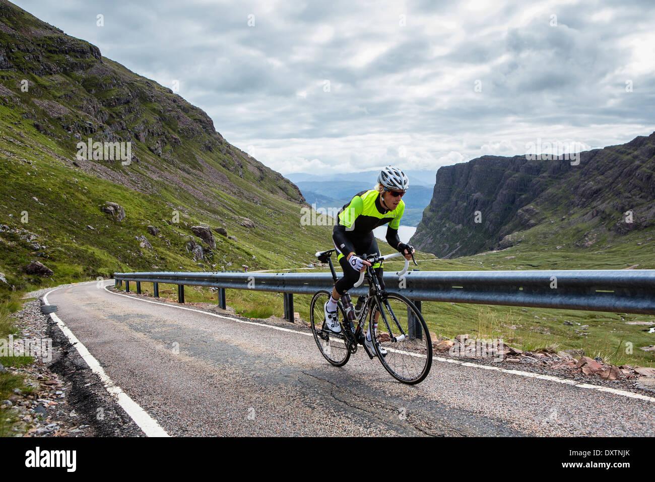 Un ciclista lleva a Gran Bretaña la carretera más larga subida en Lochcarron, Escocia Imagen De Stock