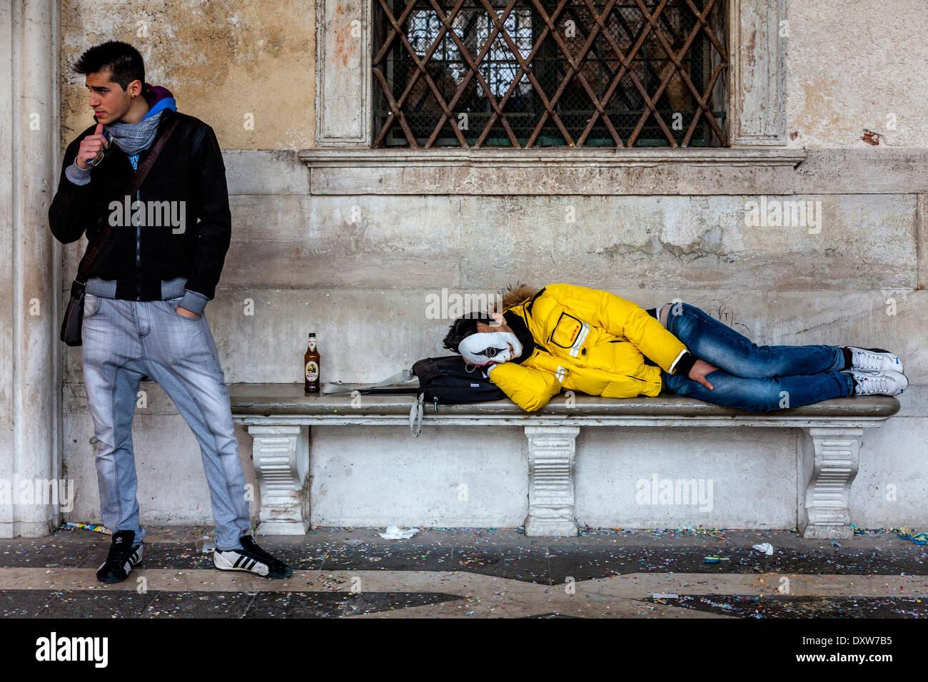 Hombre durmiendo en un banco público, la Plaza de San Marcos, el Carnaval de Venecia, Venecia, Italia Imagen De Stock