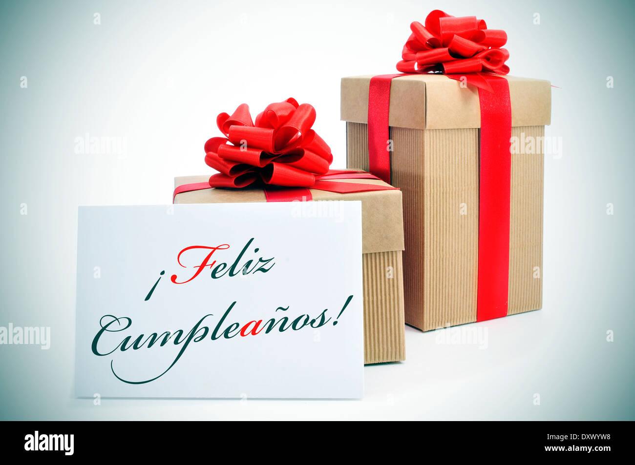 Algunos regalos y el texto feliz cumpleanos, feliz cumpleaños escrito en español en un cartel Imagen De Stock