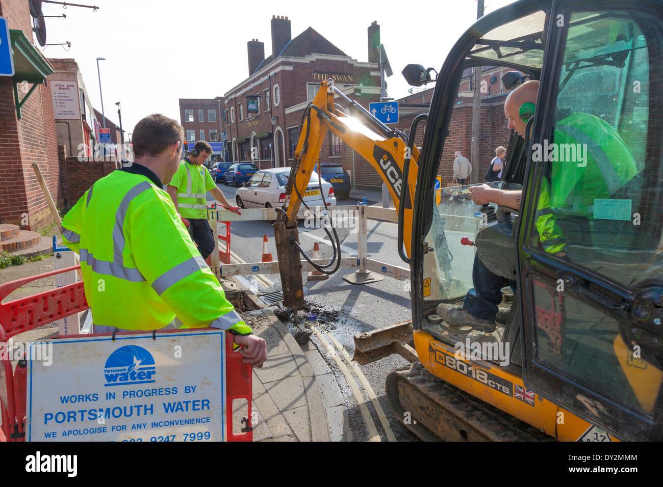 Obreros de la empresa de agua de excavar hasta road, en el centro de la ciudad. Imagen De Stock