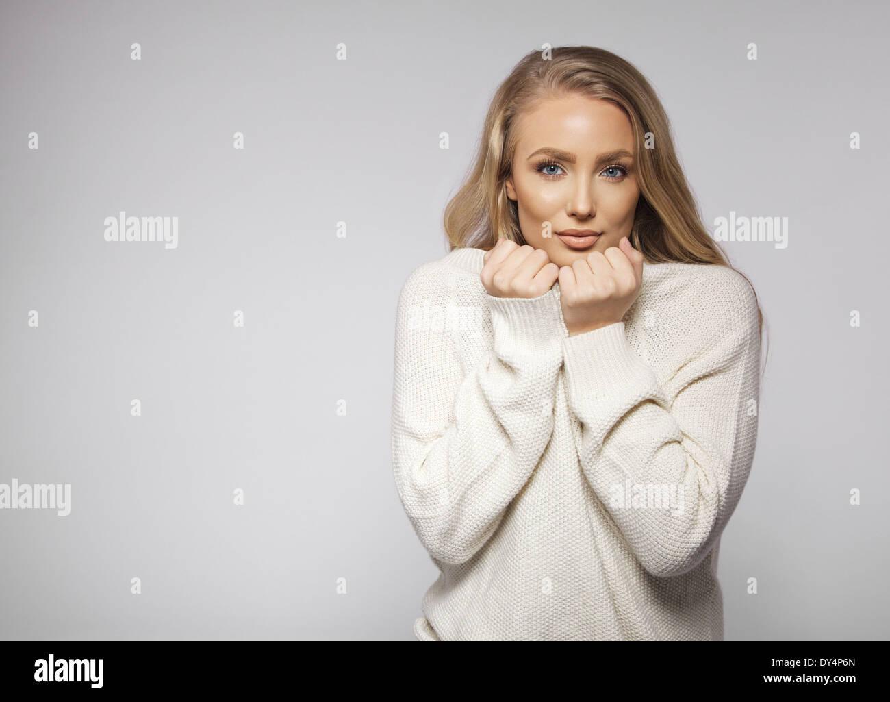 Retrato de la hermosa joven rubia vistiendo suéter la sensación de frío. Lindo modelo de moda femenina joven posando sobre fondo gris. Imagen De Stock