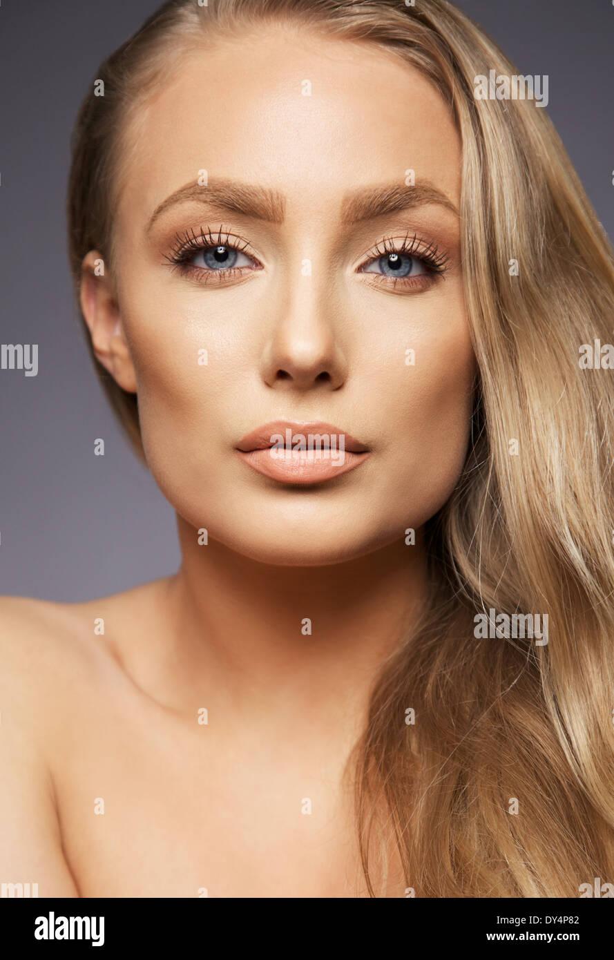 Close Up retrato de mujer bonita rubia sobre fondo gris. Rostro perfecto y maquillaje. Mirando a la cámara. Imagen De Stock