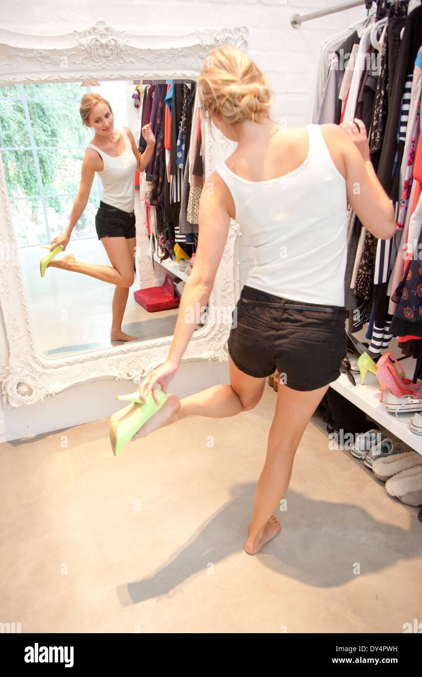 Mujer en el armario mirando en el espejo probándose zapatos Foto de stock
