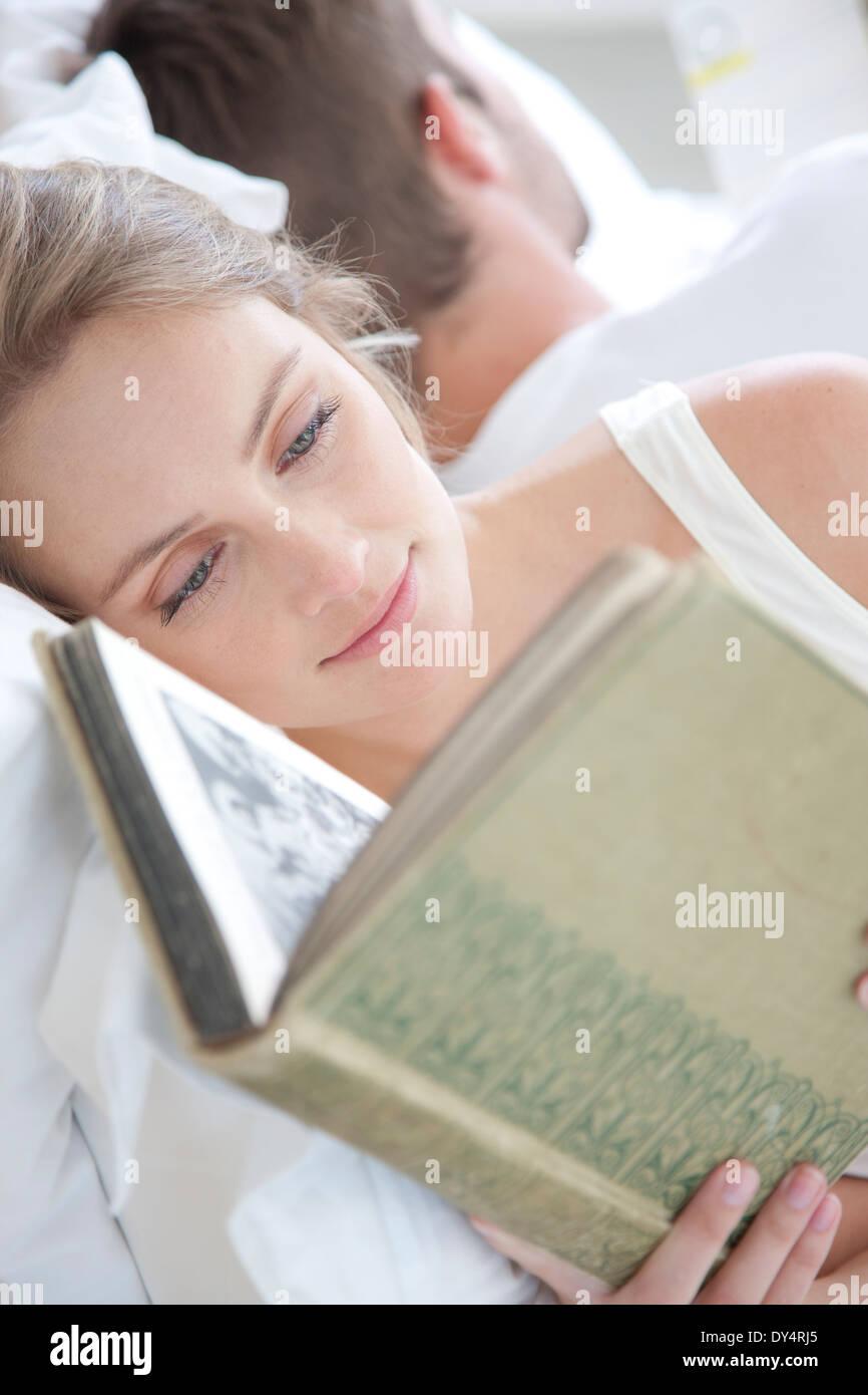 Mujer leyendo en la cama Foto de stock