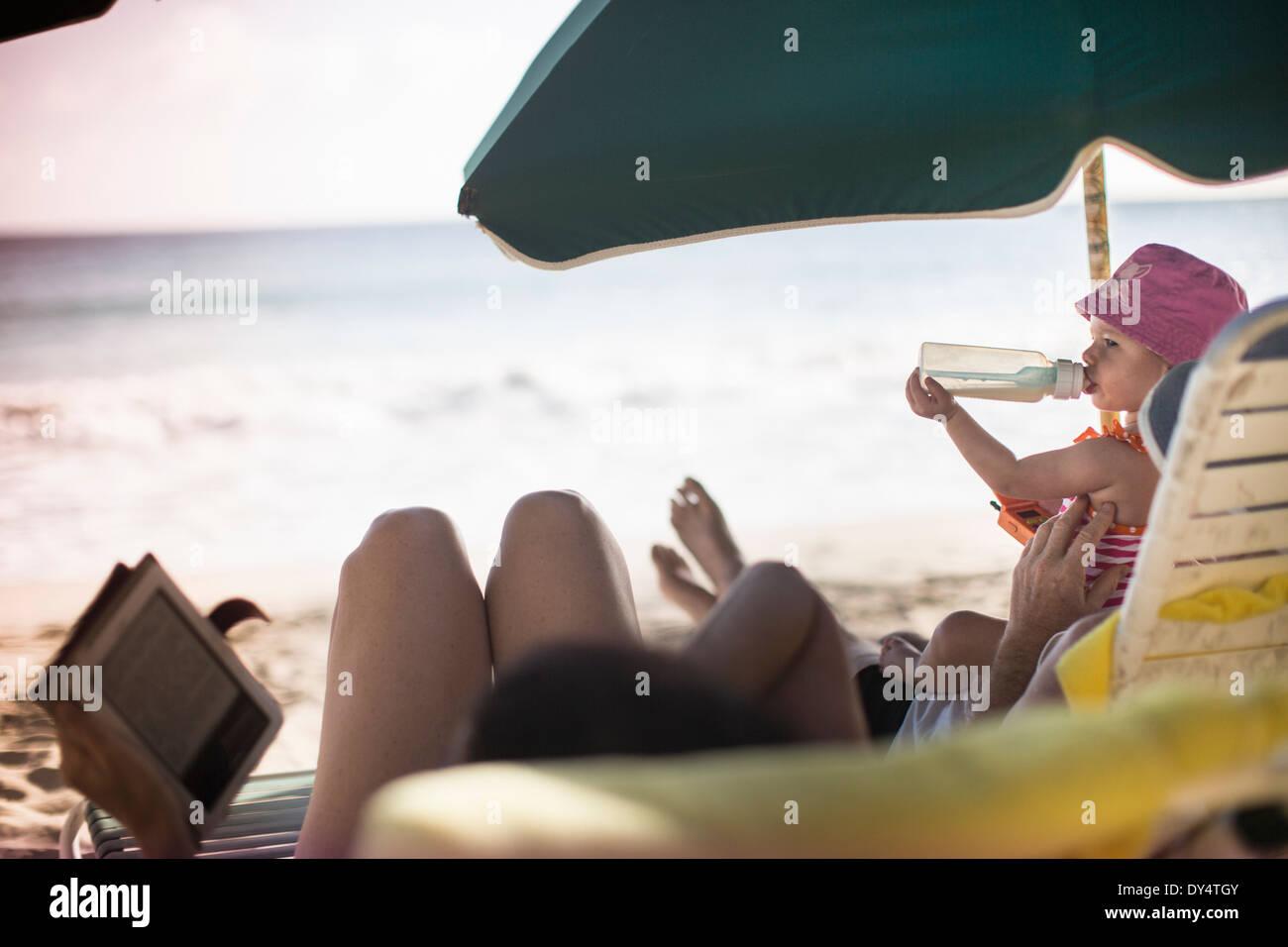 Familia tumbado en las hamacas, leer y tener una bebida Imagen De Stock