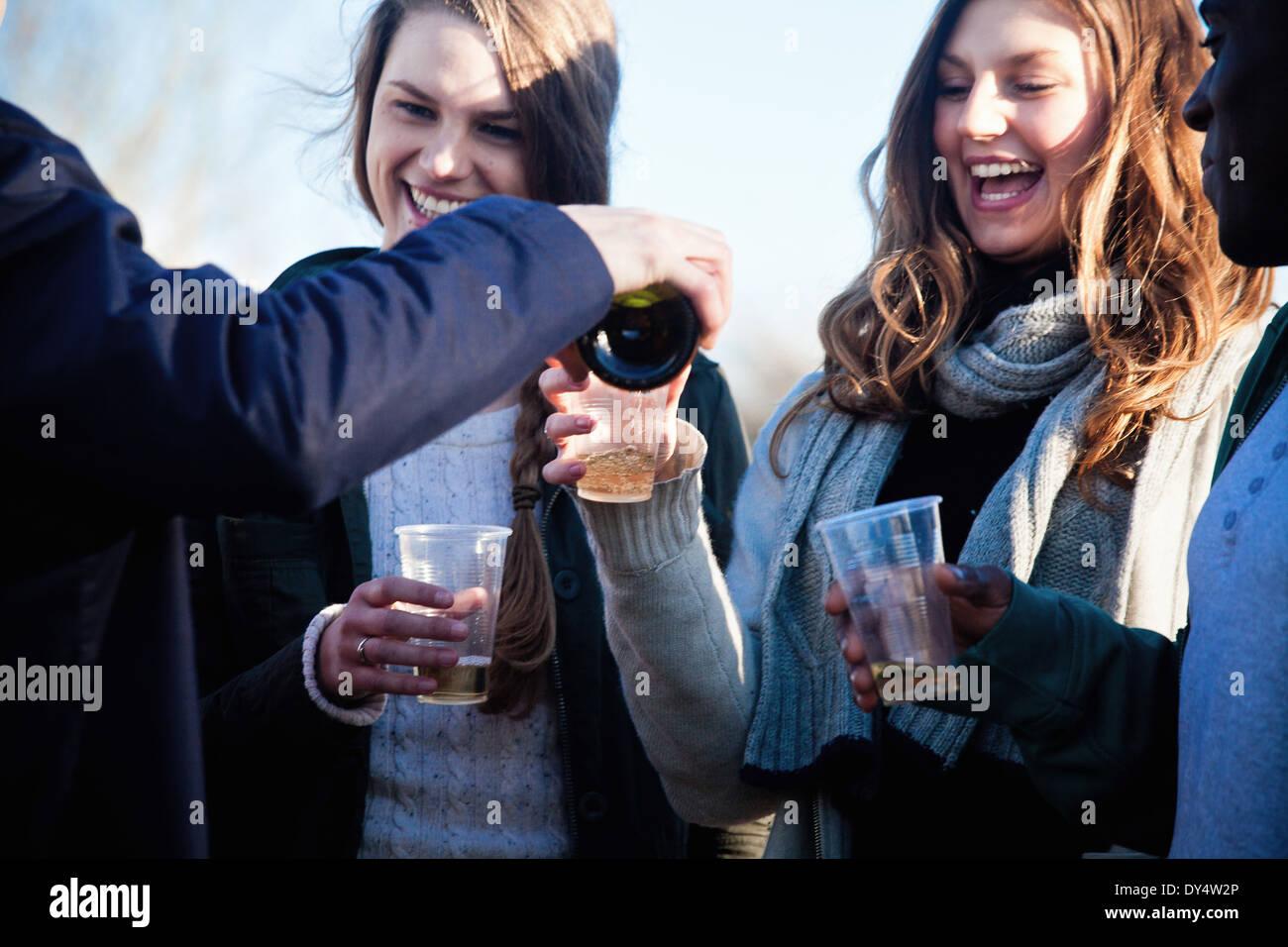 Adultos jóvenes amigos disfrutando de vino blanco en el exterior Imagen De Stock