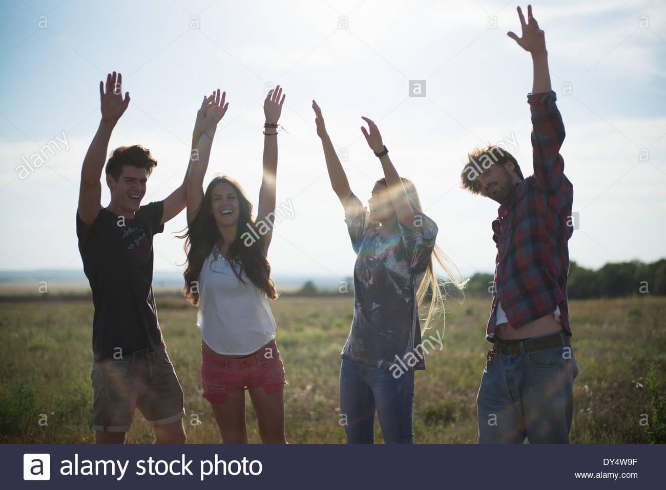 Cuatro amigos con los brazos levantados, sonriendo Imagen De Stock