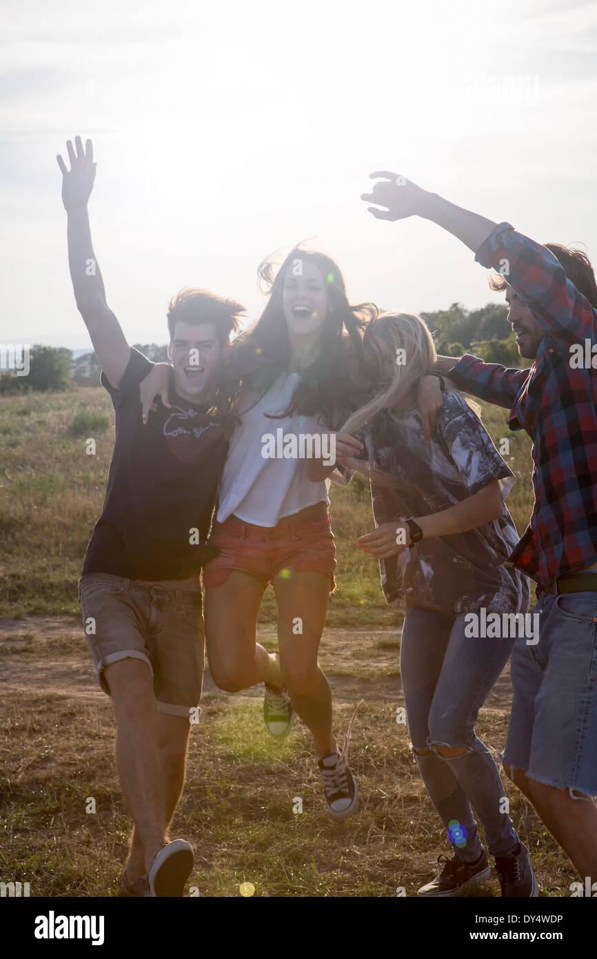 Cuatro amigos saltando con los brazos levantados Imagen De Stock