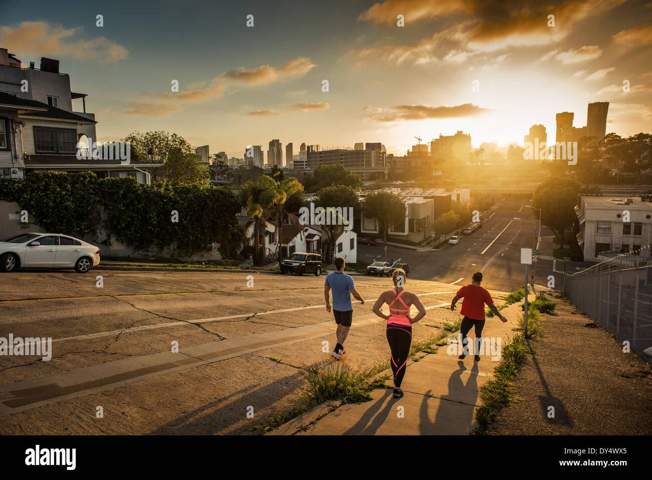 Equipo de corredores corriendo por una empinada colina de la ciudad Imagen De Stock