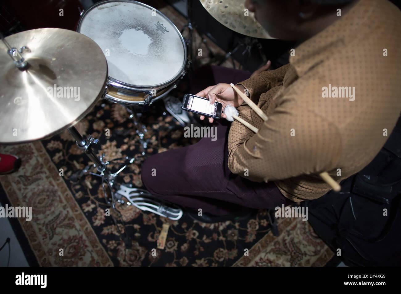 El baterista sentado en drum kit, utilizando teléfonos inteligentes. Imagen De Stock