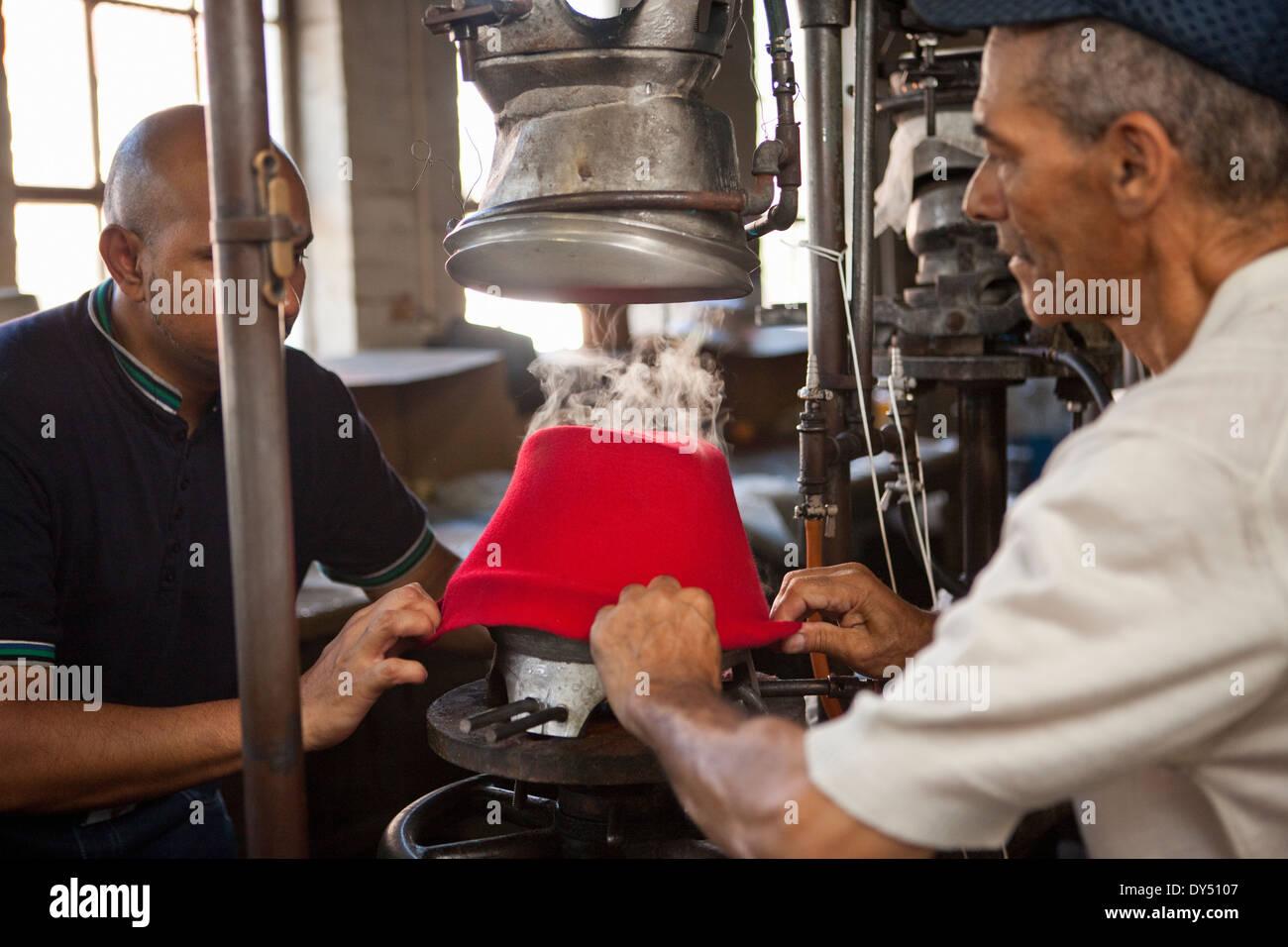 Hat makers tirando de tela en el molde en el taller Imagen De Stock