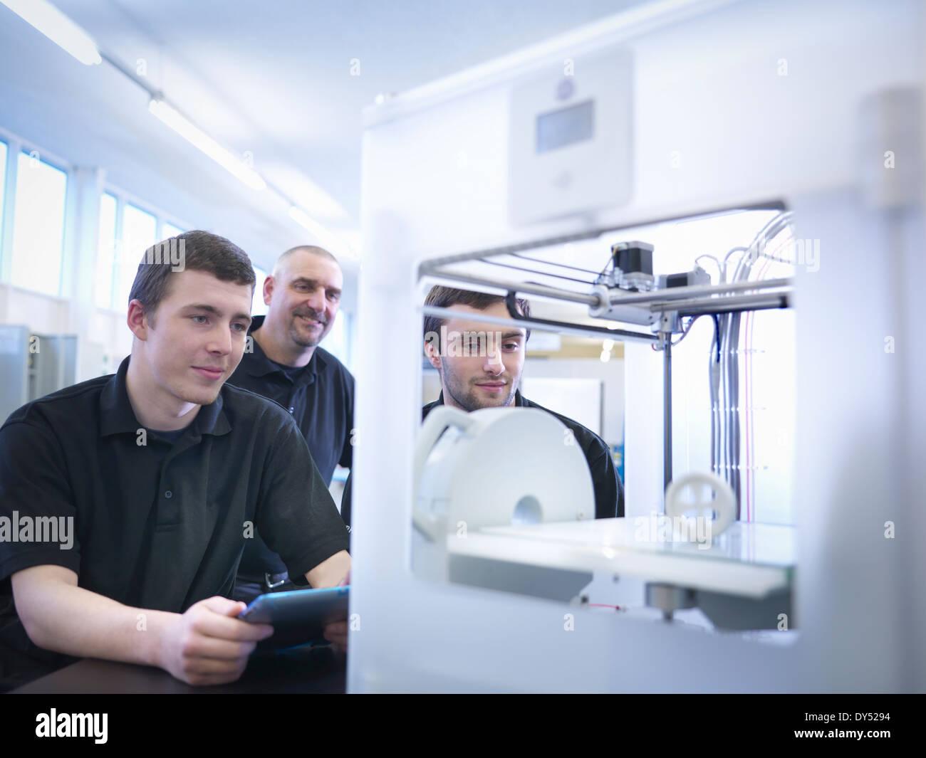 Instructor con los aprendices y máquina de impresión 3D Imagen De Stock