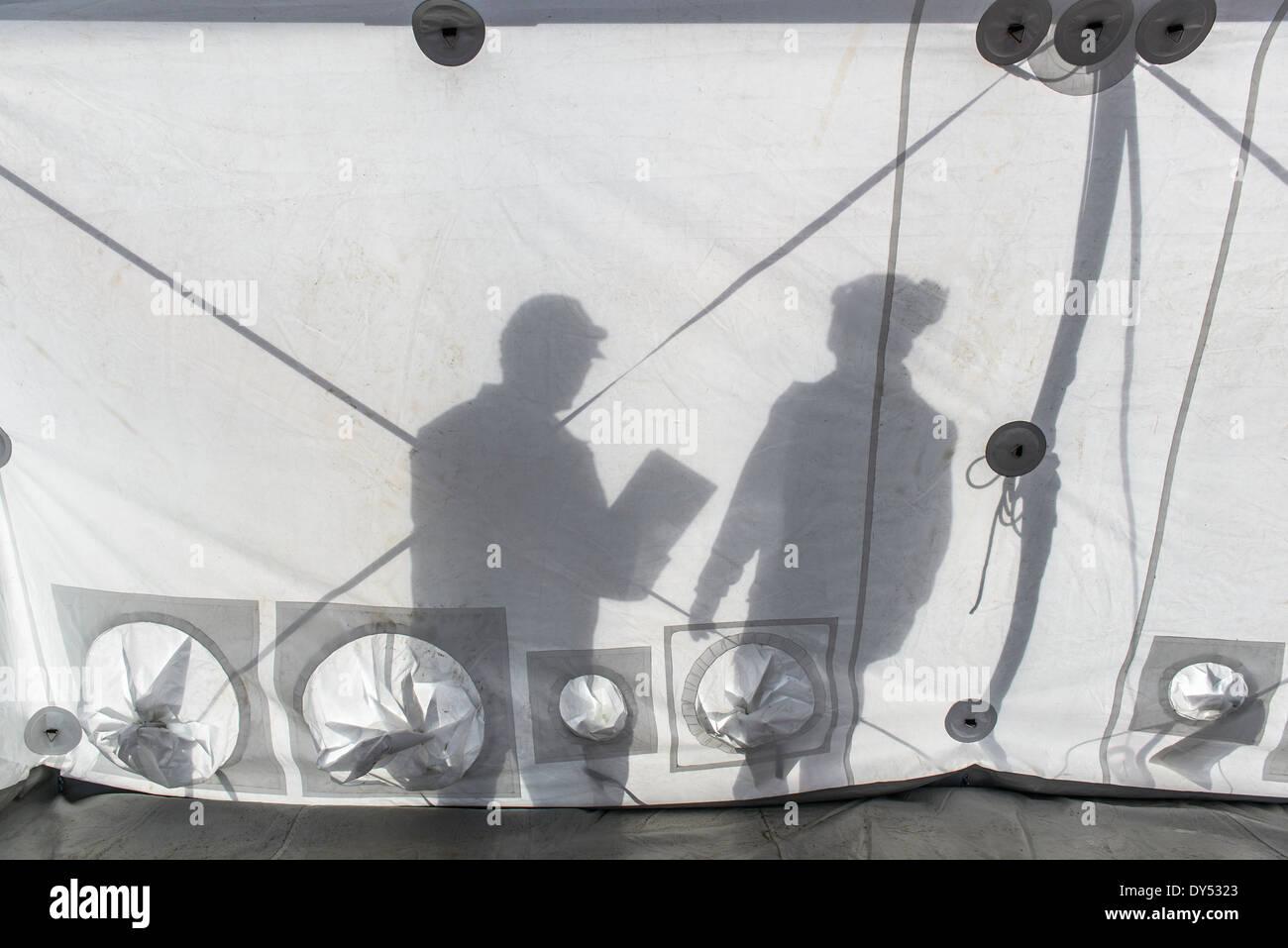 Silueta de equipo de respuesta de emergencia de los trabajadores dentro de la carpa del centro de control Imagen De Stock