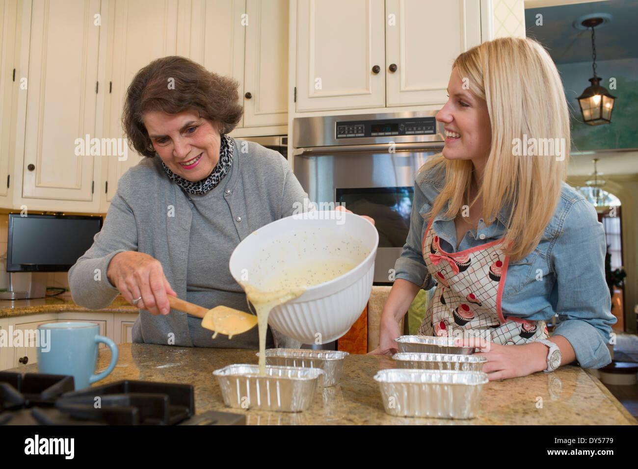 Mujer mayor y su nieta verter la mezcla en los moldes Imagen De Stock