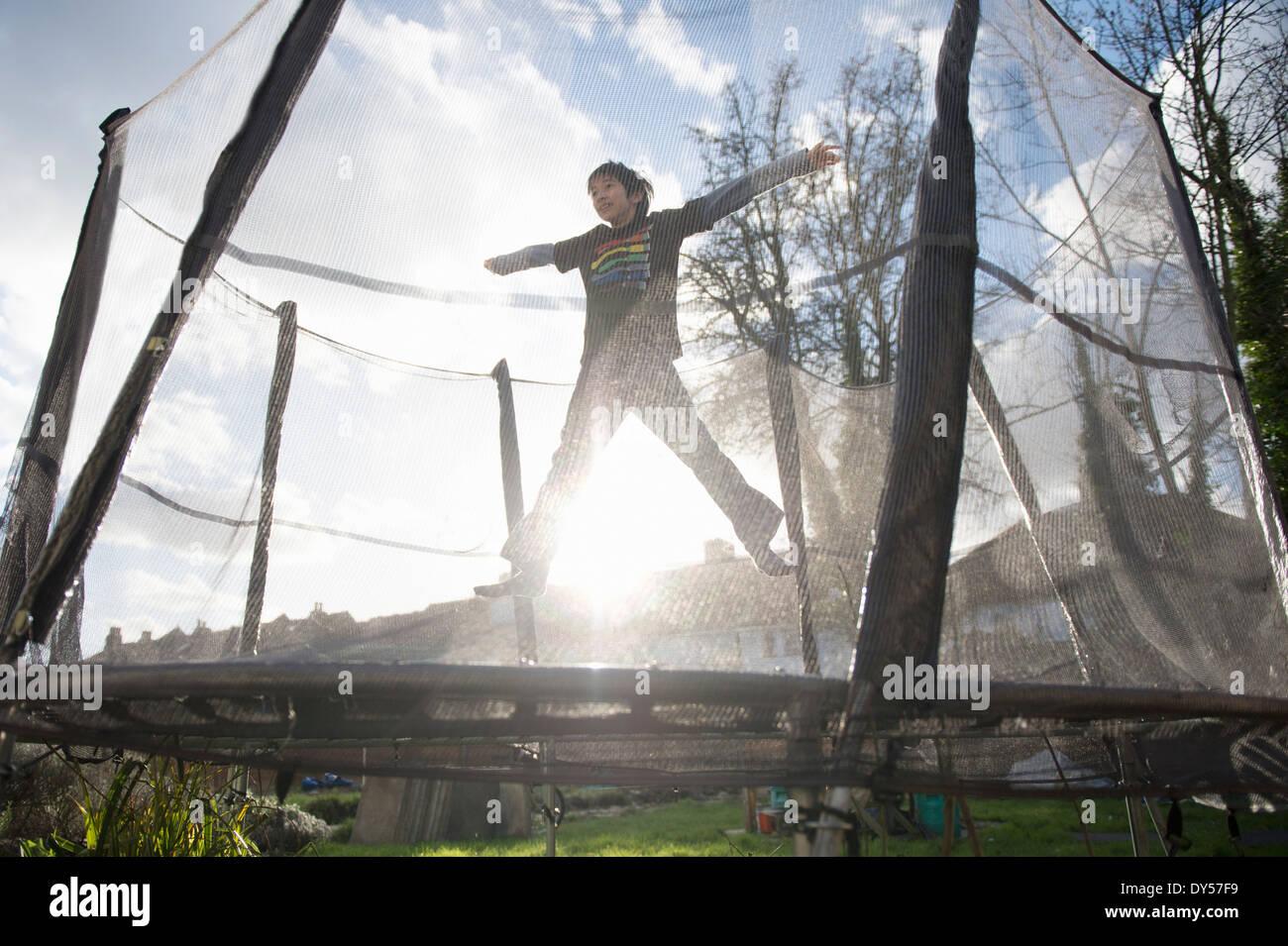Chico saltando en trampolín de exterior Imagen De Stock