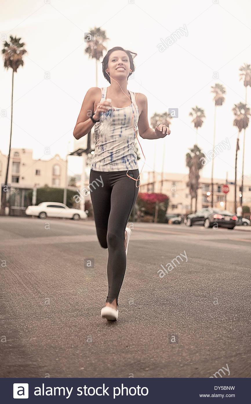 Joven Mujer atlética corriendo y escuchando auriculares Imagen De Stock