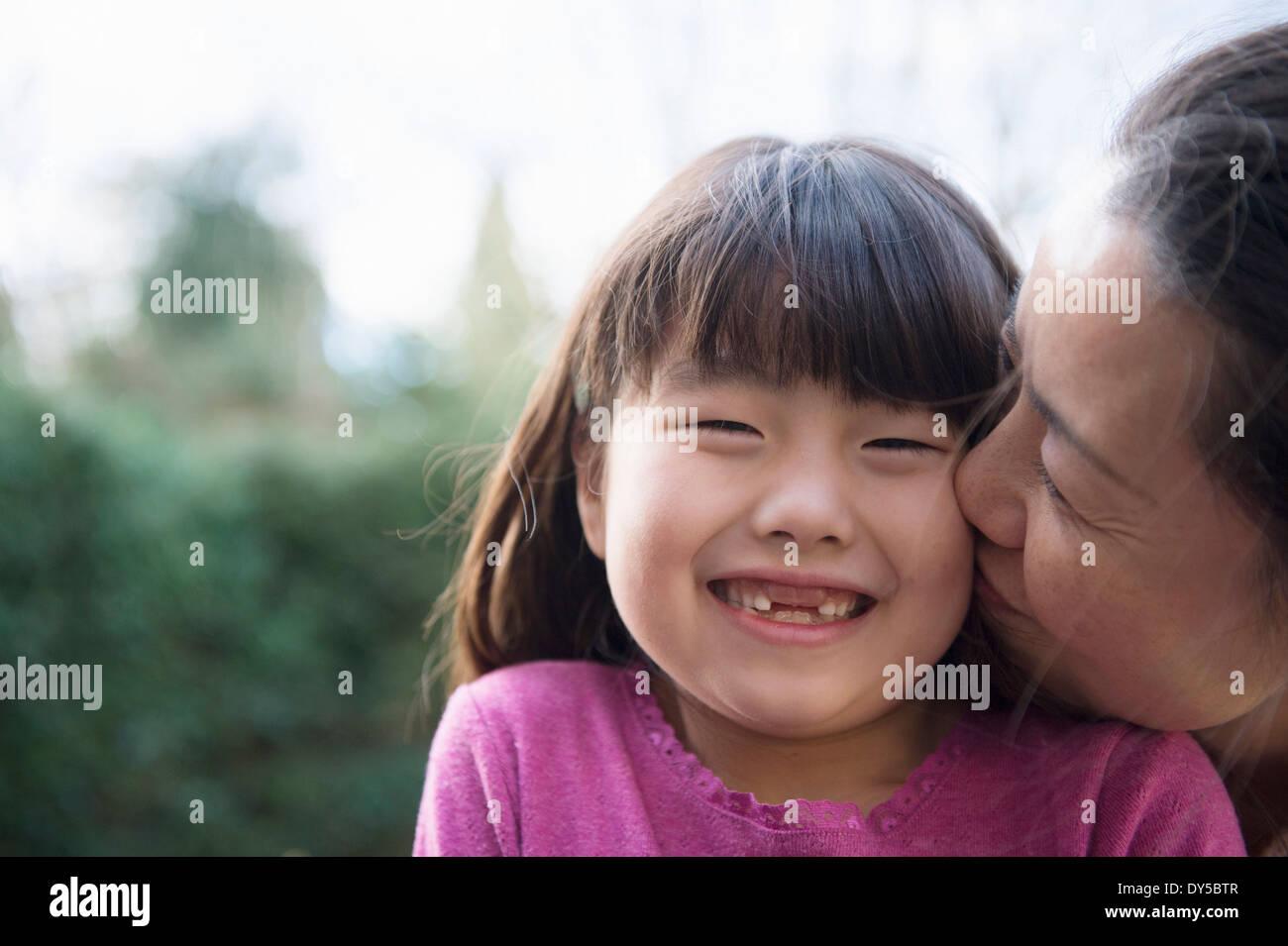 Chica ser besado en la mejilla por su madre en el jardín Imagen De Stock