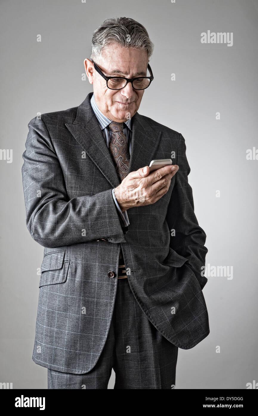 Hombre senior a través de teléfono móvil Imagen De Stock