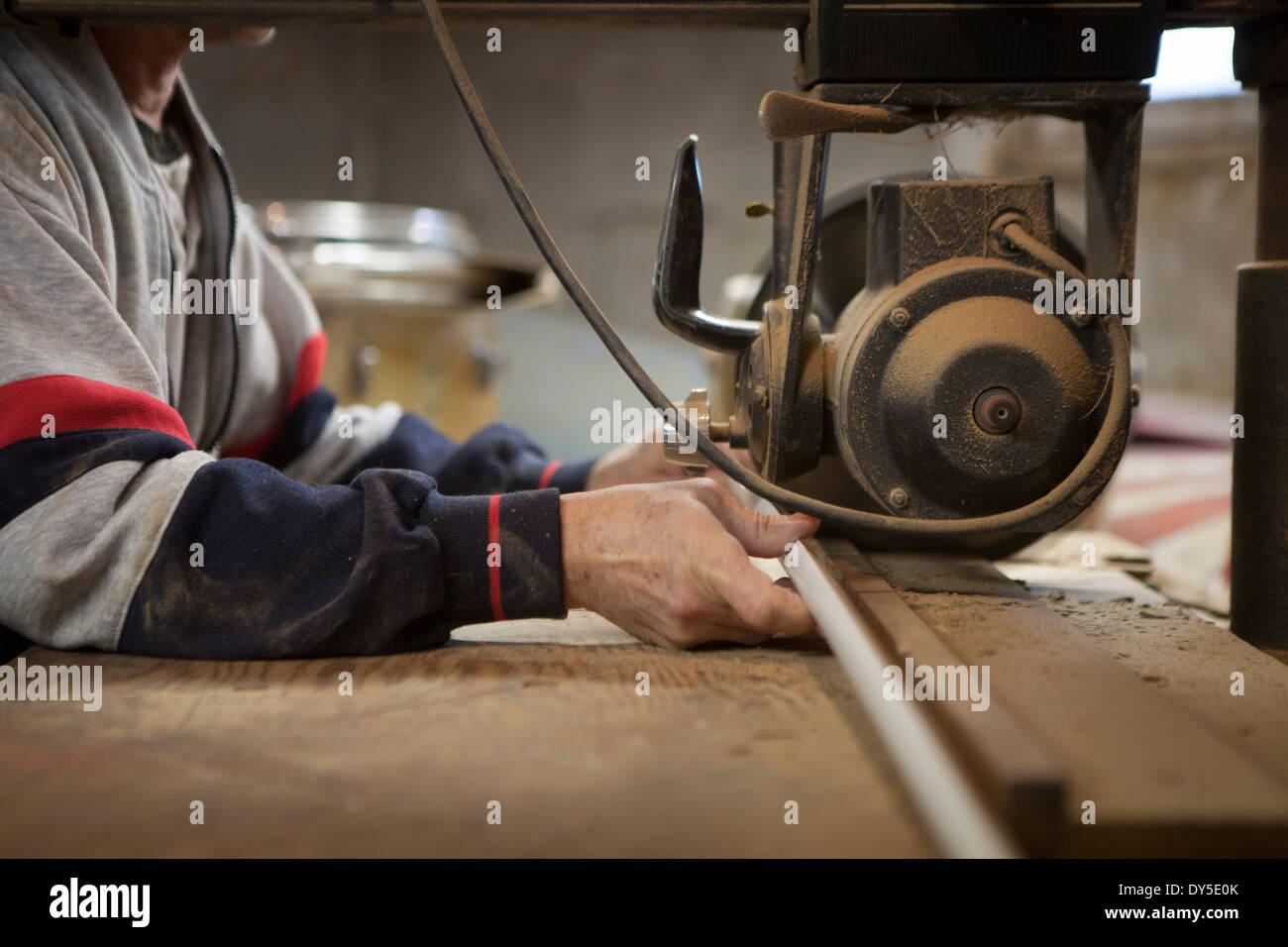 Cerca del hombre con sierra de brazo radial en el taller Imagen De Stock