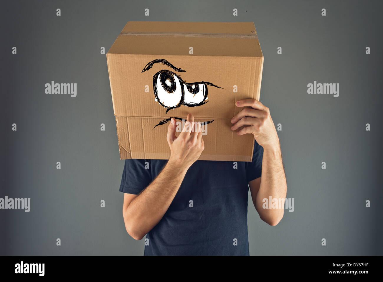 Hombre pensando con caja de cartón en la cabeza con expresión de cara seria. Imagen De Stock