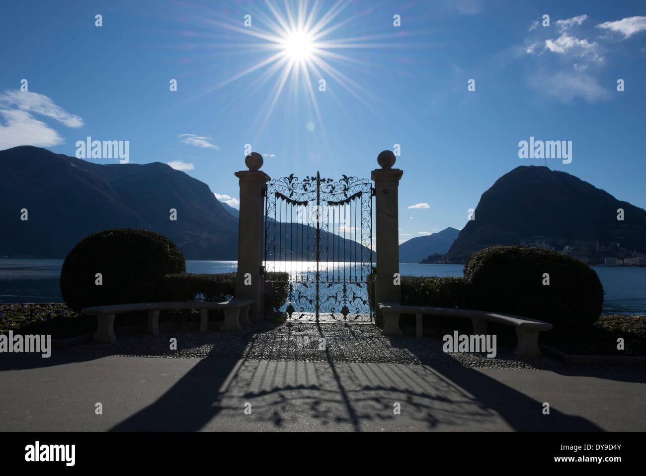 La compuerta de un lago alpino en retroiluminados con sunbeam y montaña en Lugano Suiza Ticino, Europa Foto de stock