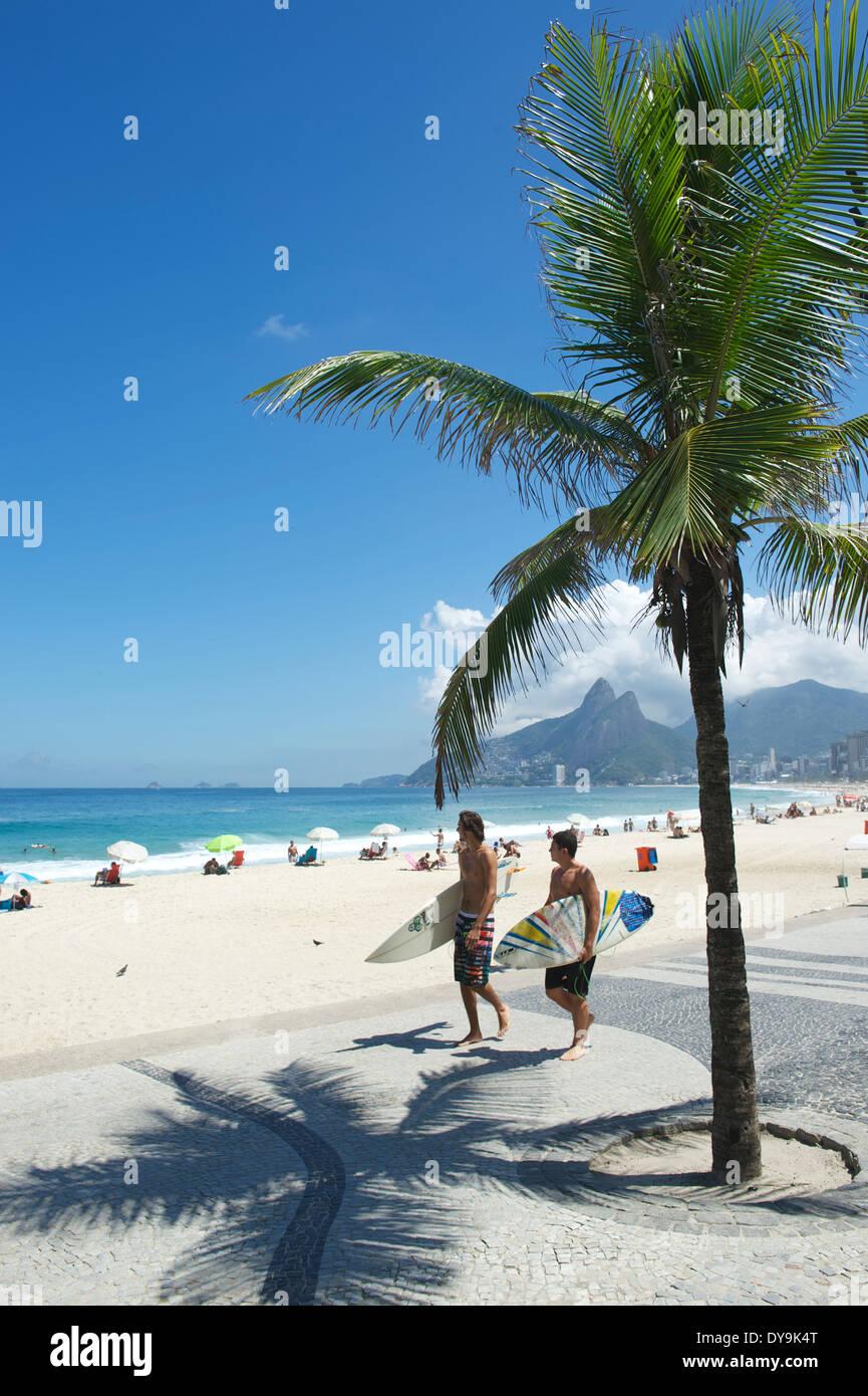 RIO DE JANEIRO, BRASIL - Marzo 28, 2014: pareja de jóvenes brasileños caminar con tablas de surf hacia el popular surf point Arpoador Imagen De Stock