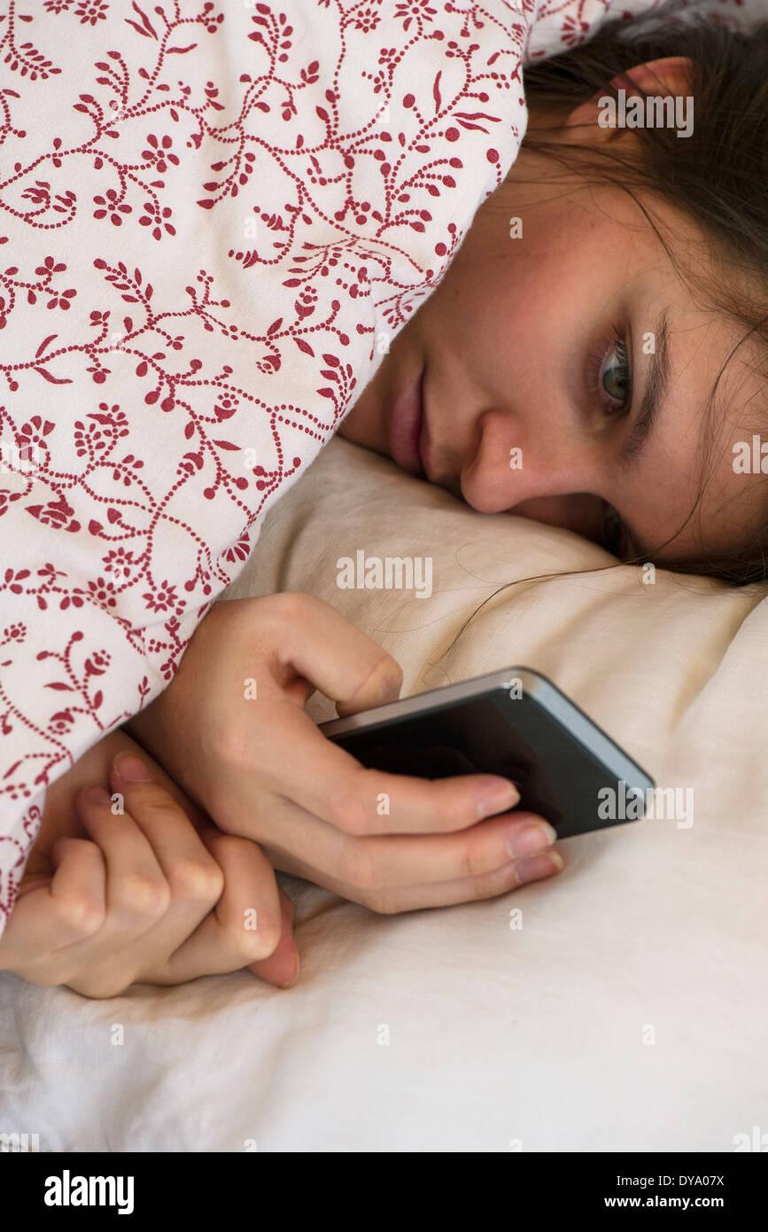 Mujer recostada cama mirando smartphone con expresión infeliz en la cara Imagen De Stock
