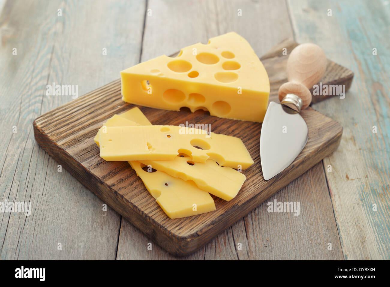 Queso con agujeros grandes y un cuchillo sobre la tabla de cortar de madera Imagen De Stock
