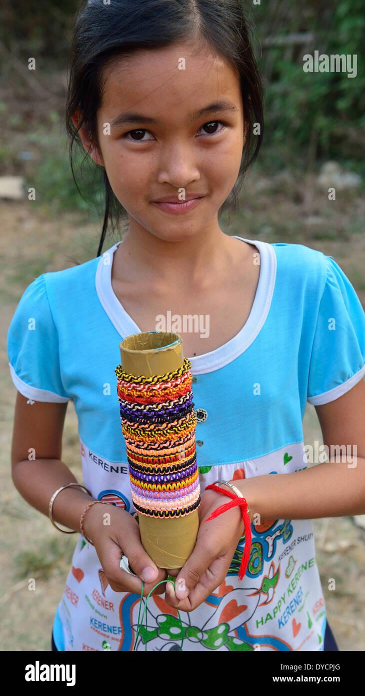 Joven camboyana ofrece su césped pulseras y anillos.joyas para venta a pasajeros de tren de bambú en la aldea de O Sra lav Imagen De Stock