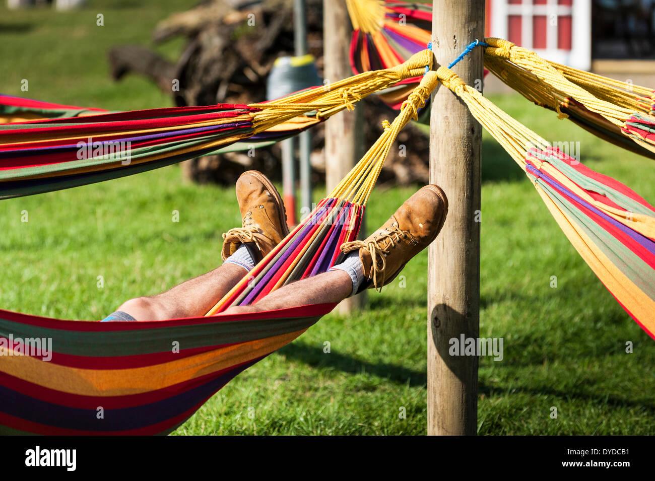 Un hombre dormido en una hamaca en el Festival Brownstock en Essex. Imagen De Stock