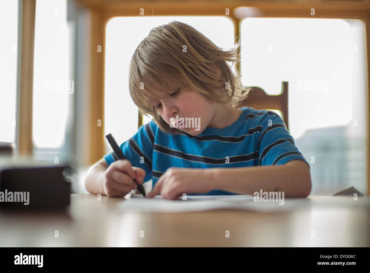Niño de siete años en la mesa de dibujo. Imagen De Stock